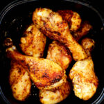 An overhead shot of cooked air fryer chicken legs in the air fryer basket.