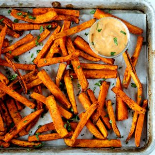 A close up, overhead shot of air fryer sweet potato fries on a baking sheet with fry sauce off to the sides.