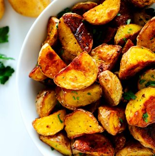 Roasted Baby potatoes in a white bowl with fresh potatoes off to the side.