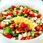 Pico de gallo in a white bowl with a chip dipped in it.