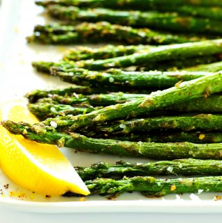 Air fryer asparagus on a white plate with a lemon wedge off to the side.