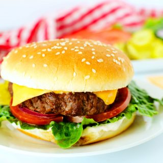 Air fryer burgers with cheese and vegetables on a white plate with a checkered red towel in the background.