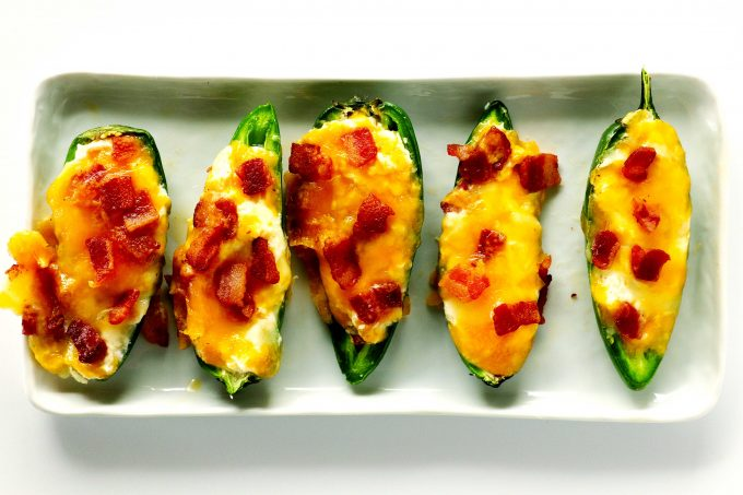 An overhead shot of Jalapeno Poppers in a line on a white, rectangle platter.