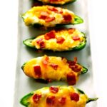 Jalapeno Poppers in a line on a white, rectangle platter.