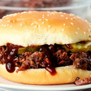 A chopped beef sandwich on a white plate.