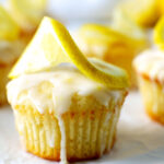 A lemon muffin with a sliced lemon decoratively placed on the top.
