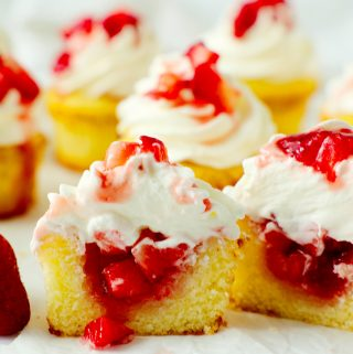 A group of strawberry shortcake cupcake cut in half with strawberries spilling out the center.