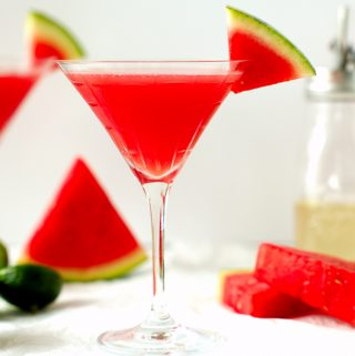 Two watermelon martinis on a white surface with limes and watermelon wedges surrounding them.