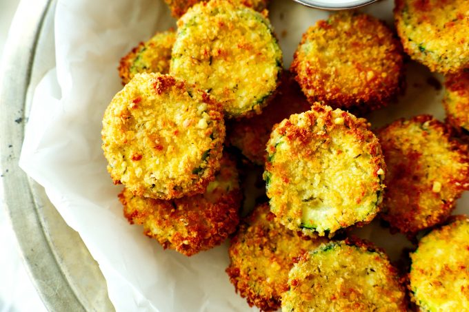 An overhead shot of zucchini chips in a basket with a white paper liner.