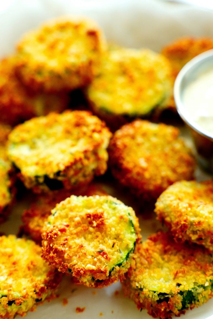 Air fryer zucchini chips with a dip off to the side.