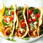 Three shredded chicken tacos on a plate surrounded by cilantro sprigs and sliced jalapenos. The tacos are topped with sliced jalapenos, sour cream, pico de gallo, and cilantro.