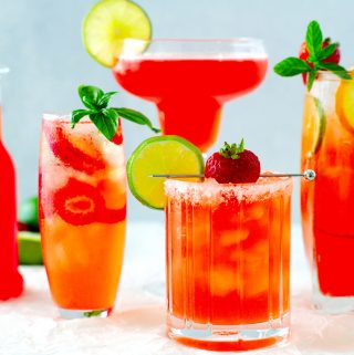 Four different strawberry cocktails in row with strawberry simple syrup off to the side.