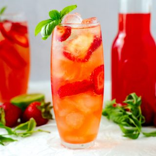 Strawberry Basil Cocktail with simple syrup, vodka, and champagne in the background.