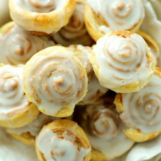 And overhead shot of puff pastry cinnamon rolls stacked in a metal pie dish.