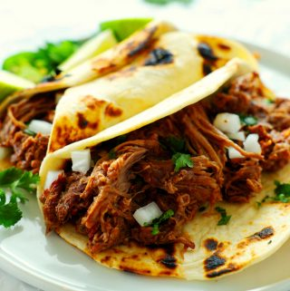 Two shredded beef tacos on a plate with one open-faced.