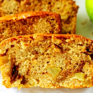 A close-up shot of apple cinnamon bread with cinnamon swirls showing and bits of Apple.
