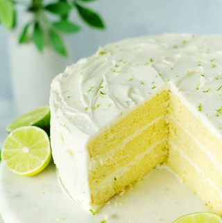 Key Lime Cake with a slice cut out of it.