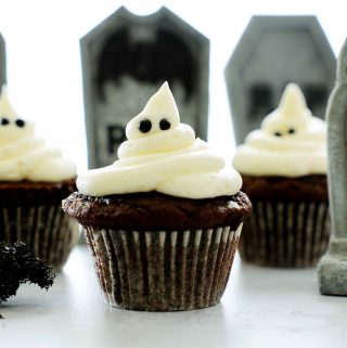 Three ghost cupcakes on a white surface with graves behind them.